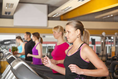 A group of four young women and a young man exercising in a fitness studio with running on treadmills