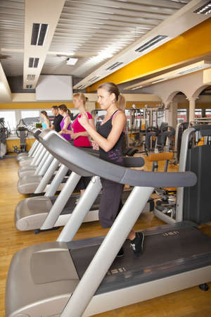 A group of four young women and a young man exercising in a fitness studio with running on treadmills photo