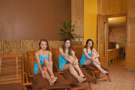 lounger: Three smiling beautiful young women with towels sitting on loungers in front of a sauna and looking at camera