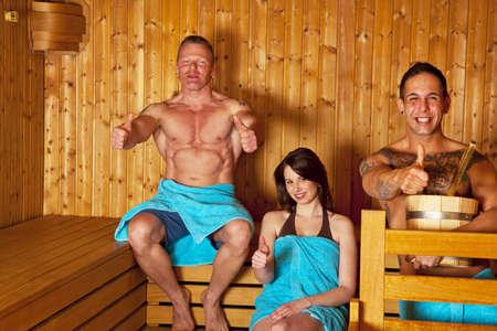 Eine junge Frau und zwei Männer mit Handtüchern sitzen in einer Sauna und posiert mit den Daumen nach oben unterzeichnen Standard-Bild