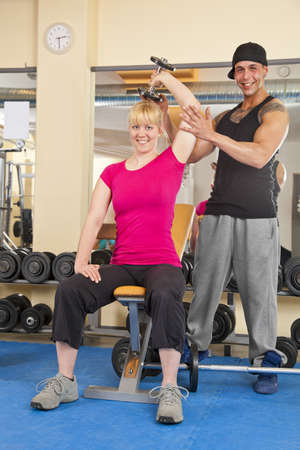 A smiling beautiful young woman in her twenties exercising in a fitness studio training her triceps and being instructed by her personal trainer, both looking into camera photo