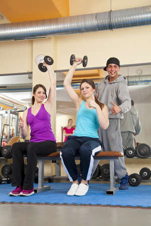Two smiling beautiful young women exercising in a fitness studio training her triceps and being instructed by her personal trainer, all posing with the thumbs up sign photo