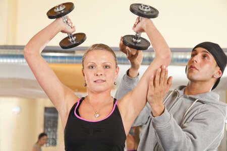 A smiling beautiful young woman in her twenties exercising in a fitness studio training her triceps and being instructed by her personal trainer photo