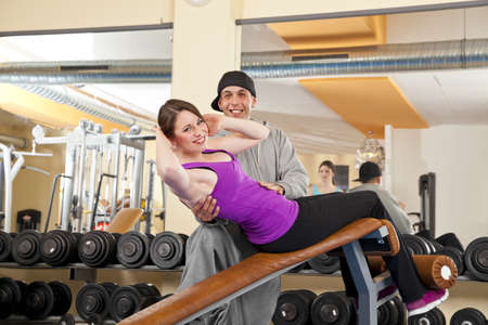A smiling beautiful young woman in her twenties exercising in a fitness studio training her abdominal muscles and being instructed by her personal trainer, both looking into camera photo