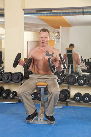 male age 40's: A man in his forties exercising in a fitness studio training his biceps and looking at camera
