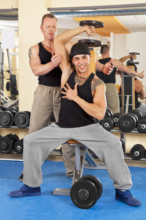 A handsome young man in his twenties  exercising in a fitness studio training his triceps and being instructed by his personal trainer