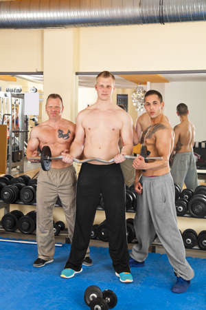 A handsome young man in his twenties  exercising in a fitness studio training his biceps and being instructed by his personal trainers, all looking at camera photo