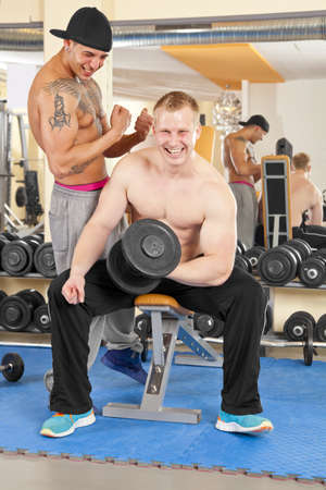 A smiling handsome young man in his twenties exercising in a fitness studio training his biceps and being instructed by his personal trainer photo