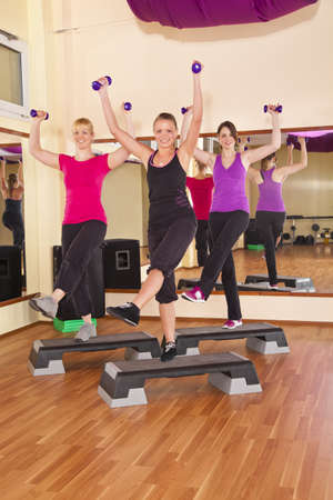 Three smiling beautiful young women exercising aerobics in a fitness studio with dumbbells and aerobics stepper Stock Photo