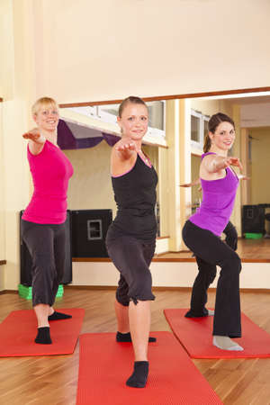 gymnastics equipment: Three beautiful young women performing stretching exercises in a fitness studio and looking at camera