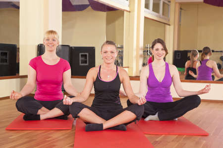 Three beautiful young women performing yoga exercises in a fitness studio and looking at camera