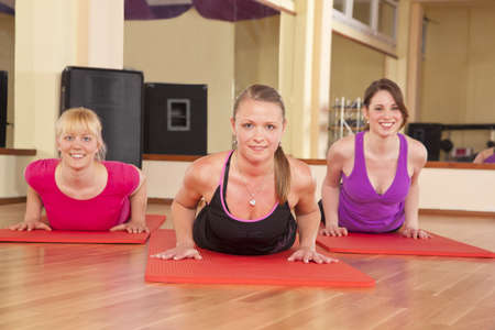 Three beautiful young women performing stretching exercises in a fitness studio and looking at camera