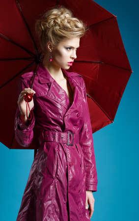 Young woman with umbrella on blue 版權商用圖片
