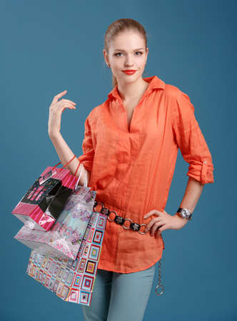 girl in an orange shirt and jeans with shopping bags photo