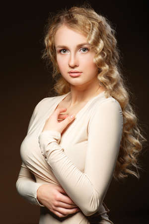 Lovely model with shiny volume curly hair. Nude makeup. Long hair. On a beige background. photo