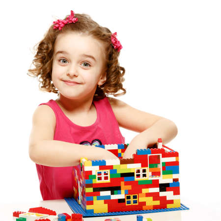 Small girl builds a house from plastic blocks.