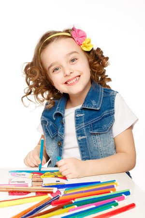 Cheerful little girl with felt-tip pen drawing in kindergarten. photo