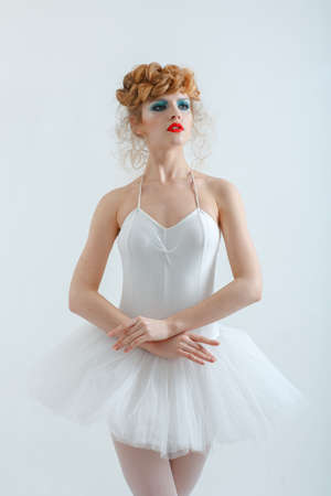 Portrait of a beautiful girl with fashion makeup - red lips, stylish hairstyle. In ballet dress. Tutu. photo