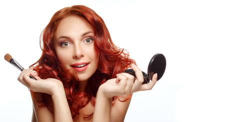 Makeup. Cosmetic. Beauty portrait of pretty ginger woman with brush for makeup and powder. Applying Make-up. photo