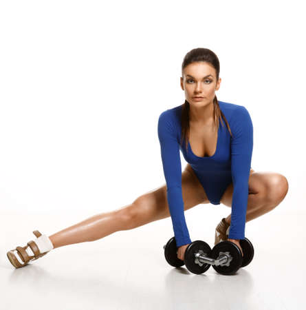 muscle women: Woman bodybuilder in blue bodysuit, performs an exercise with dumbbells  Studio shot