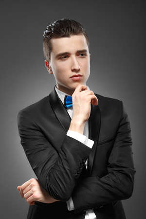 lost in thought: Young man is standing lost in thought Stock Photo