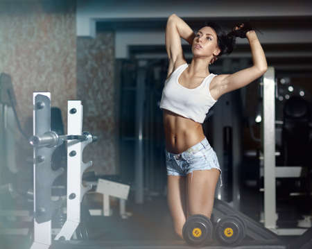 Young sexy woman after workout in gym  photo
