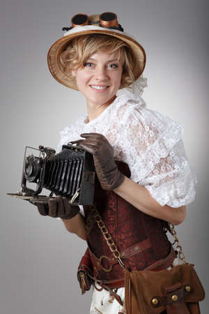 Beautiful happy woman with retro camera. Steampunk. photo