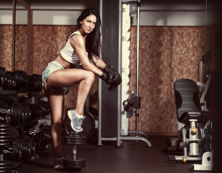 Sexy girl with boxing gloves posing in the gym photo