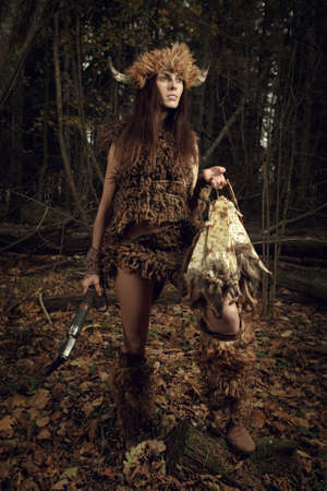 sibyl: Ancient woman hunter in the forest with an ax in his hand. Historical costume. Stock Photo