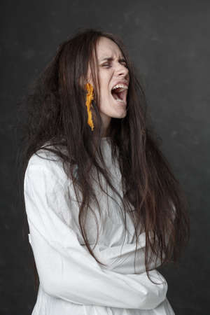 Crazy woman screaming in a straitjacket photo