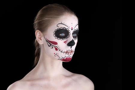 Woman with dia de los muertos makeup, black empty space photo