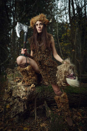 sibyl: The ancient woman in the forest with an ax in his hand. Halloween. Historical costume.