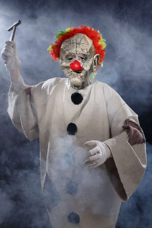 Scary monster clown with hammer photo