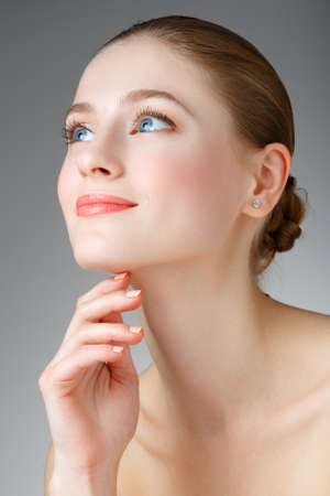 Beautiful Woman Touching her neck. Perfect Fresh Skin. Pure Beauty Model. Youth and Skin Care Concept. Smiling girl with blue eyes. Portrait of a beautiful woman with a smile.
