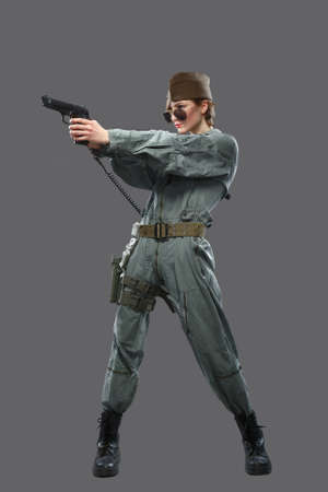helicopter pilot: A girl dressed as a helicopter pilot with a gun in his hand isolated on grey background
