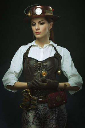 victorian lady: PortraBeautiful girl steampunk. Posing with the small clock.