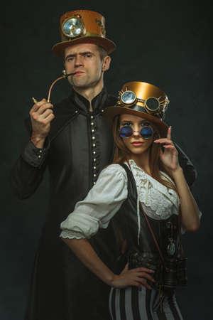 steam machine: El steampunk pareja. Un hombre con un tubo y una chica con gafas y sombrero.