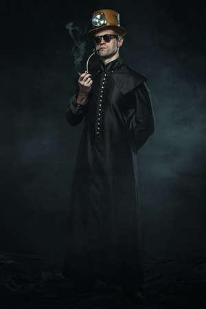 MAQUINA DE VAPOR: Steampunk hombre con un abrigo largo fumando una pipa
