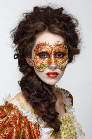 Faceart. Venetian mask. Beautiful woman in vintage dress and a mask on his face. photo