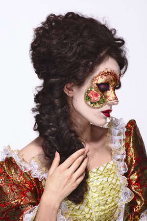 faceart: Faceart. Venetian mask. Beautiful woman in vintage dress and a mask on his face. Looking to the right. Stock Photo