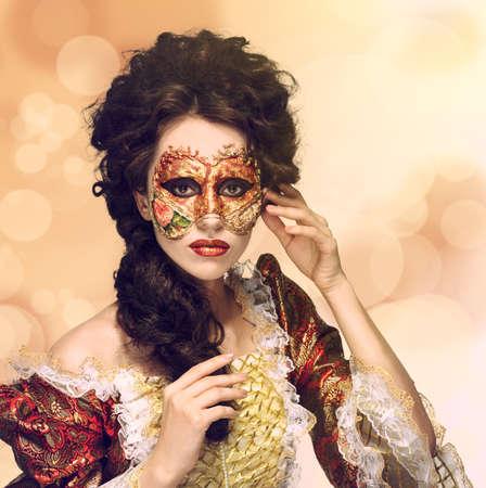 faceart: Faceart. Venetian mask. Beautiful woman in vintage dress and a mask on his face. Looking to the camera.