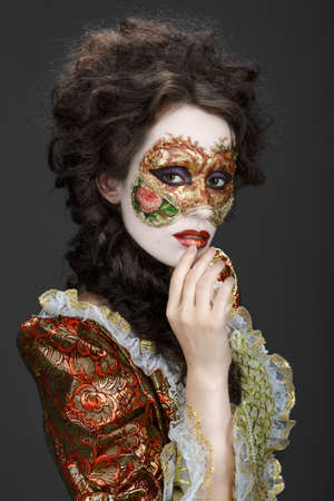 faceart: Faceart. Venetian mask. Beautiful woman in vintage dress and a mask on his face. Shy glance at the camera.