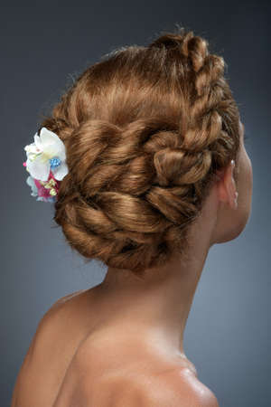 female hair: Back view of beautiful haircut with flowers. Beauty wedding hairstyle. Bride
