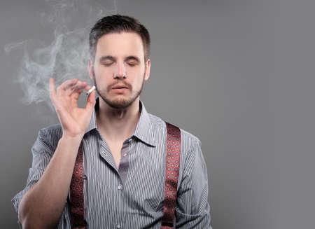 Fashion man smoking a cigarette on gray background Stock Photo
