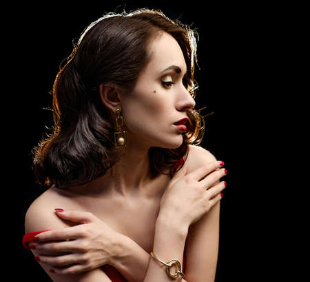 bashfulness: Beautiful girl in a red dress on a black background. Woman takes off her dress. Shallow depth of field.