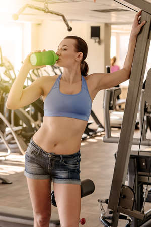 water stained: Sports girl drinks water in the gym after workout. Stained instagram.