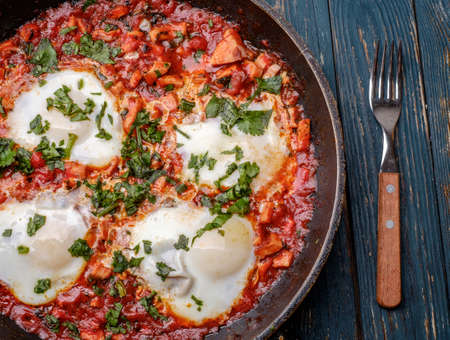 food restaurant: Fried eggs in a frying pan with tomatoes, sausage and greens.