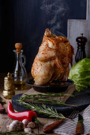 rustic food: Roasted whole chicken with spices and herbs on a wooden table. Tasty food. Rustic style.