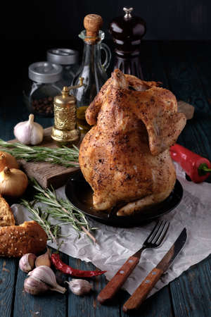 Roasted chicken with spices and herbs on a wooden table. Tasty food. Rustic style. photo