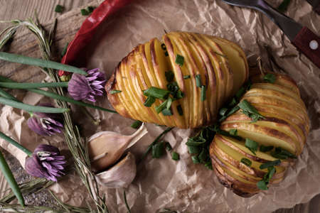 baked: Sliced baked potatoes over wooden background. Rustic style.